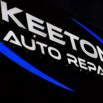 "Lighted Channel Letter Storefront Sign in Overland Park KS for Keeton Auto Repair. White letters reading ""Keeton Auto Repair"". Blue logo elements."