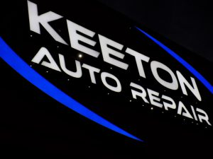 "Lighted Channel Letter Sign in Overland Park KS for Keeton Auto Repair. White letters reading ""Keeton Auto Repair"". Blue logo elements."